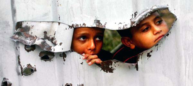 children looking through hole in barrier