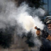 An Israeli policeman fires tear gas canisters during clashes with Palestinian protesters in the West Bank city of Hebron last week. Mussa Qawasma / Reuters